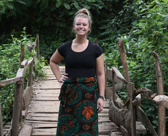 Brooklyn Loxtercamp stands on wooden bridge in a tropical forest.