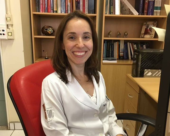 Fernanda Fernanda Raphael Escobar Gimenes de Sousa, PhD, MSN, BSN, sits in her office wearing her lab coat.